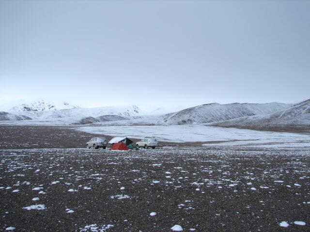 The white cook tent is anchored between two Land Cruisers, with two smaller tents in front of it. The windswept plains are sparsely covered in snow.