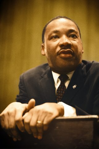 photo of Martin Luther King Jr at a lecturn with hands resting on the edge