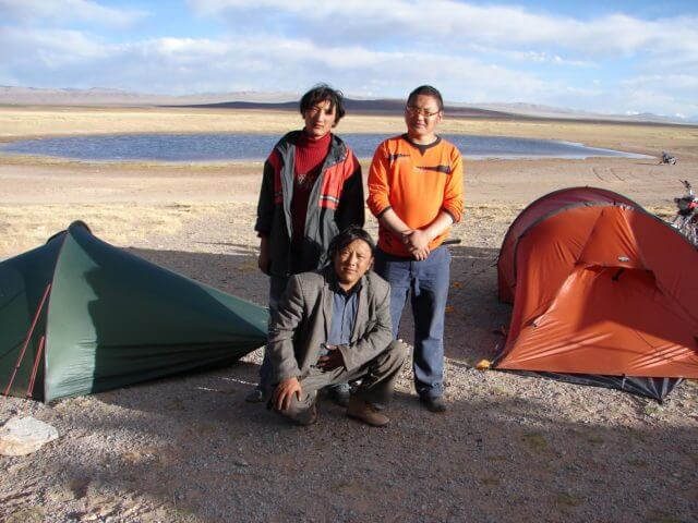 Three men stand on an open plain between two small tents.