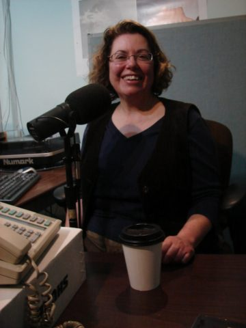 A woman sitting in front of a microphone with a coffee cup.