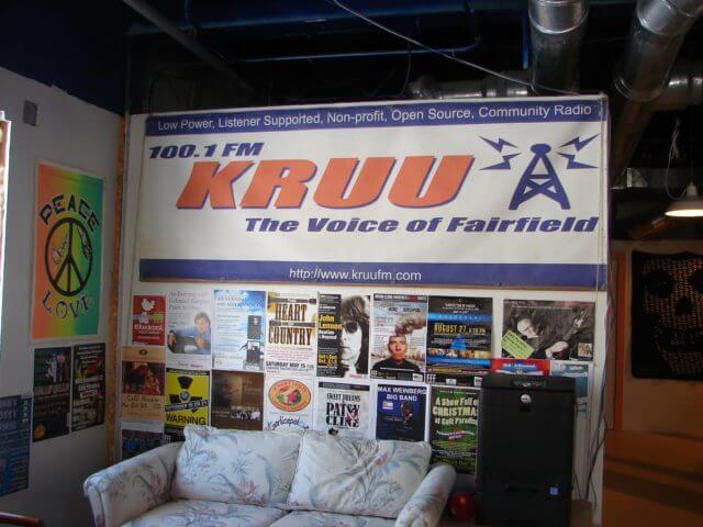 The wall of a radio station, KRUU 100.1 FM, decorated with posters.