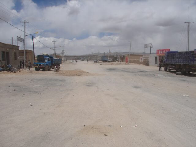 A dusty street in a town with large vehicles sporadically parked on the side.