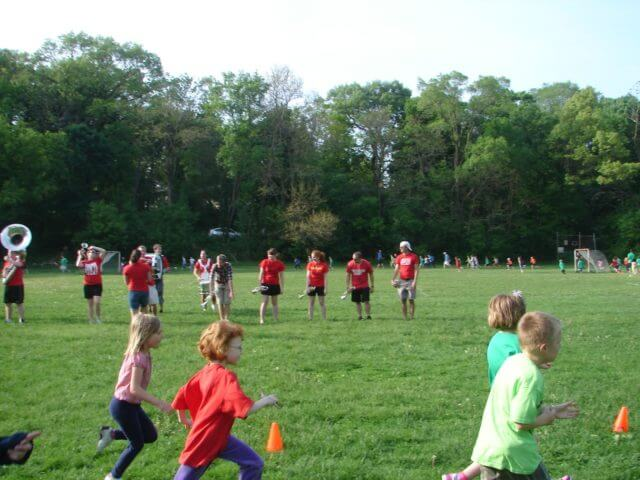 Kids running at a school picnic, a small marching band behind them.