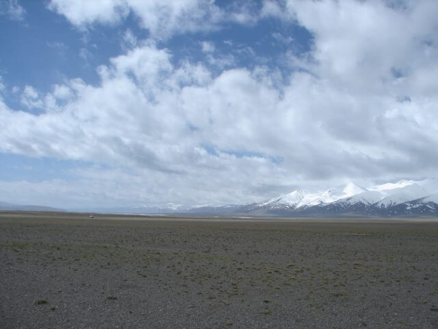 Wide plains and snowcapped mountains behind them. A truck can be faintly seen in the distance.