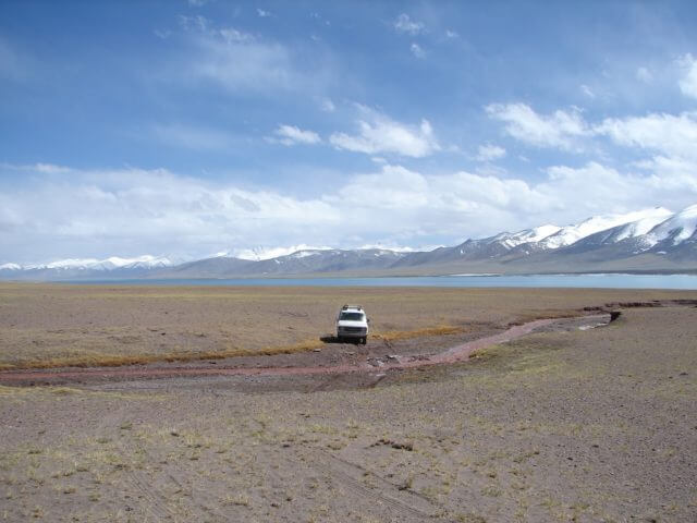 A lone truck sits in the center of wide-open plains, with a lake and mountains behind it.