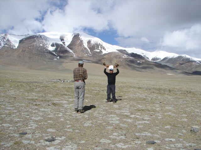Two men stand near a mountain. The one facing the camera is holding a yak skull above his head by the horns.