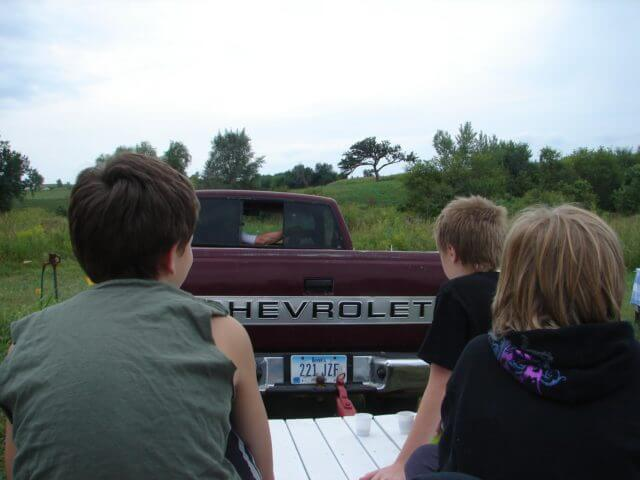 Kids riding on a trailer pulled by a pickup truck through the prairie.