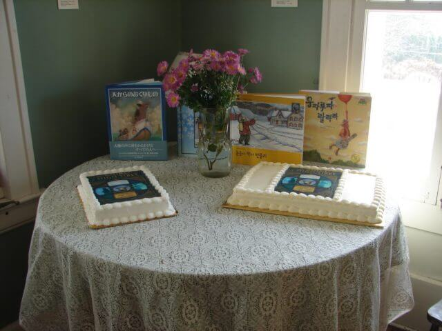 A table with 2 cakes decorated with the Chiru of High Tibet's cover, and other books written by Jaqueline in the background.