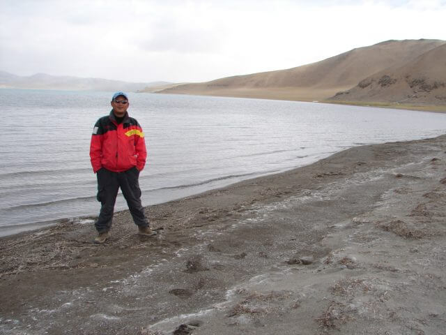 A man in a red coat standing by the lake Aru Tso