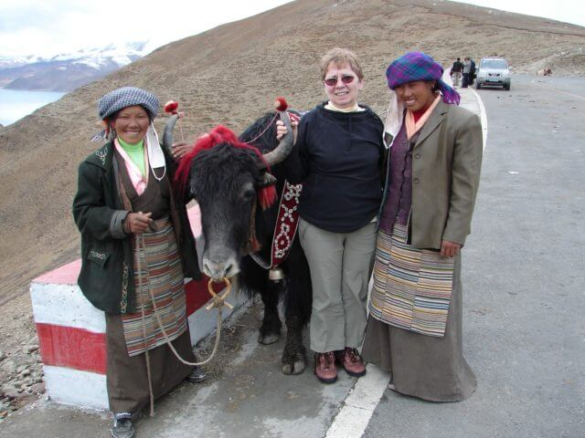 Jacqueline standing between locals on the road