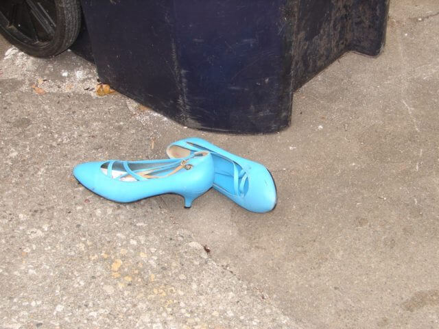 A pair of bright blue strappy shoes, discarded near a bin.