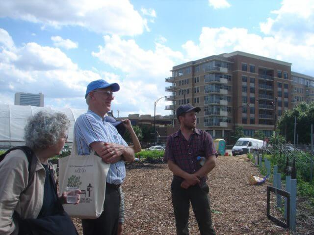 3 People stand discussing in an urban farm