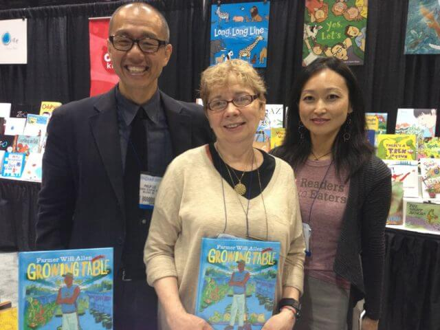 Philip Lee, Jaqueline, and June Lee pose with the cover of Farmer Will Allen.