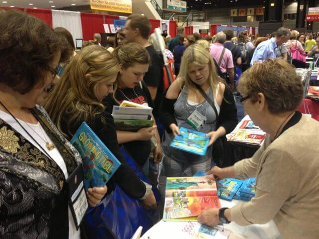 Librarians and writers looking at Farmer Will Allen and the Growing Table.