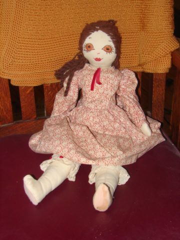 A doll sitting on a chair
